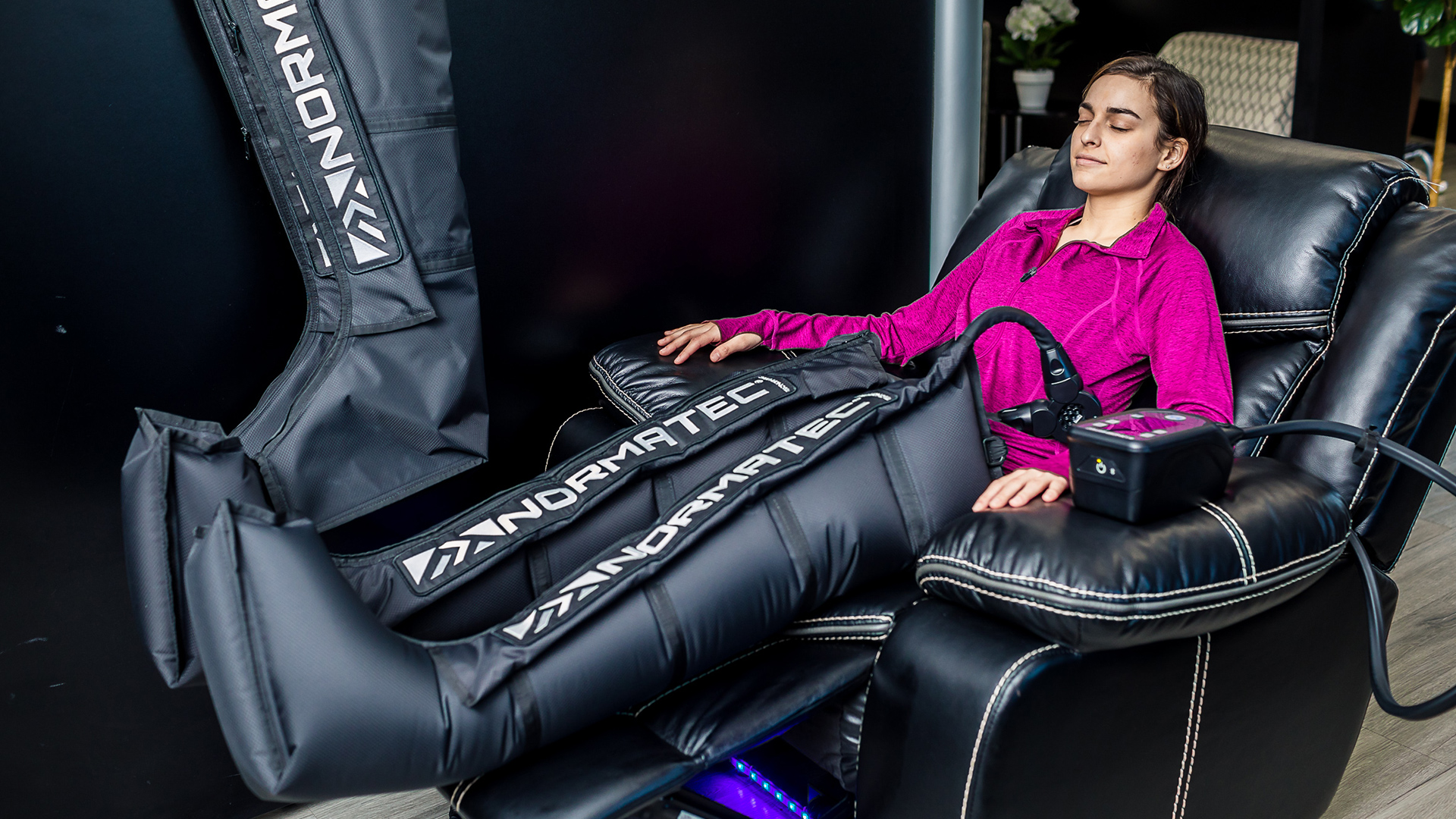 guest relaxing in a recliner with normatec leg attachments on legs