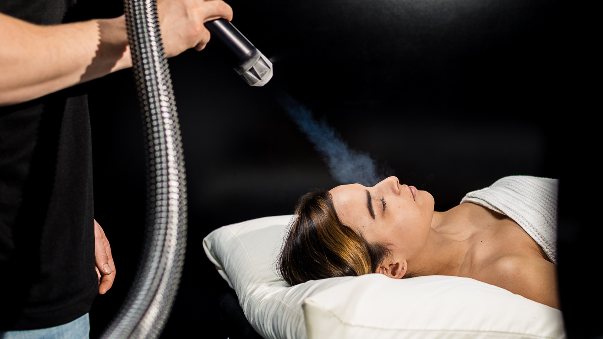attendant applying localized cryotherapy onto guest's face