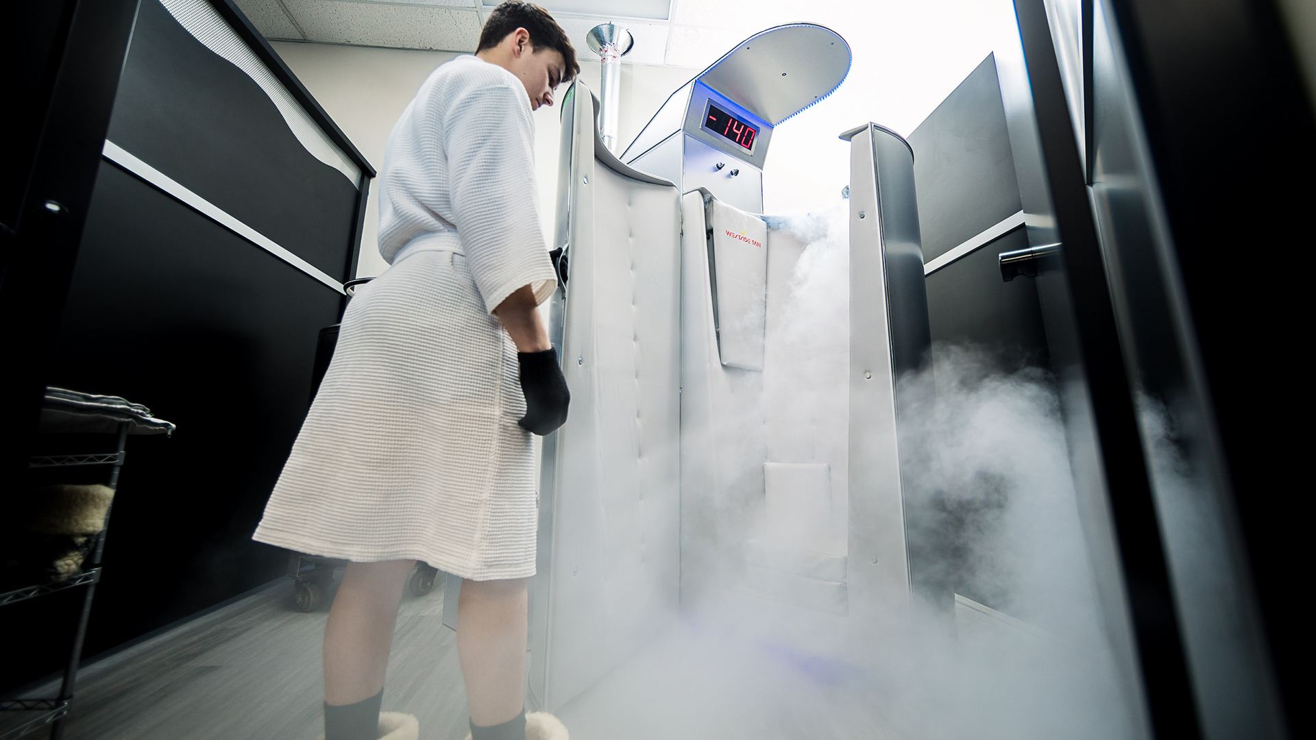 guest standing next to open cryotherapy chamber as nitrogen is being released